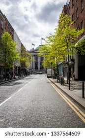 DUBLIN, IRELAND - APRIL 22, 2016: Perspective city street view with fresh green trees and incidental people in the background in Dublin Ireland April 22, 2016.