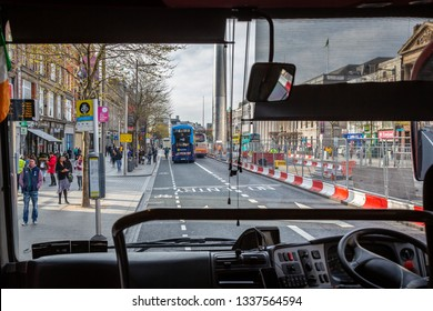 DUBLIN, IRELAND - APRIL 23, 2016: A bus drivers perspective of a busy city street seen from the inside with incidental people on the street in Dublin Ireland April 23, 2016.