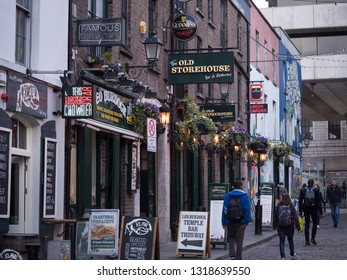 Dublin, Ireland - April 23rd 2016: Fish and chip shop, Irish pub with Guinness sign, and tourists walking in the street in Temple Bar, Dublin, Ireland