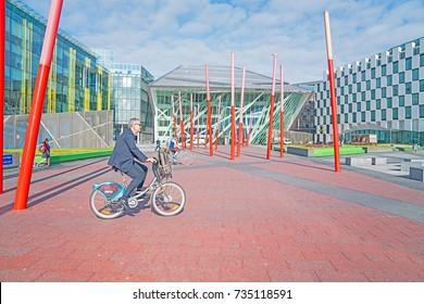 DUBLIN, IRELAND - AUGUST 10; Commuters cycle and walk through Grand Canal Square surrounded by modern architectural buildings and red pole sculpture on way to work August 10, 2017 Dublin Ireland
