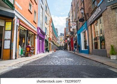DUBLIN, IRELAND - AUGUST 10;  Few people seated outside cafe and walking in shop  lined narrow quaint cobbled street in Temple Bar area with shop signage on both sides August 10, 2017 Dublin Ireland