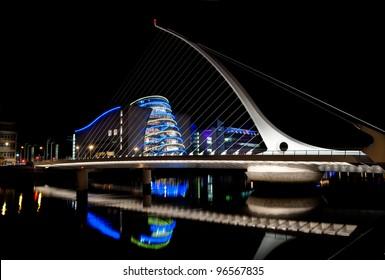 DUBLIN, IRELAND - AUGUST 23: Samuel Beckett Bridge, a cable-stayed bridge by architect Santiago Calatrava, pointing to Dublin Convention Center at nighttime, on August 23, 2011 in Dublin, Ireland