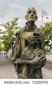 Dublin, Ireland - August 7, 2017: Great Irish Famine bronze statue set on Custom House Quay along Liffey River in Docklands. One slender male figure. Green trees and gray sky.