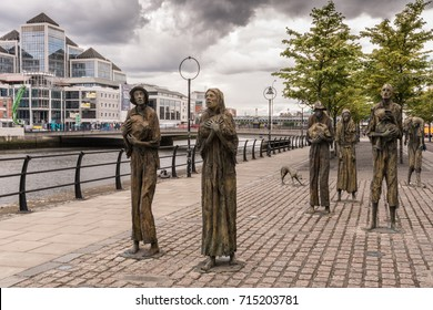 Dublin, Ireland - August 7, 2017: Great Irish Famine bronze statue set on Custom House Quay along Liffey River in Docklands. All six figures, male and female, plus dog. Green trees and cloudscape.