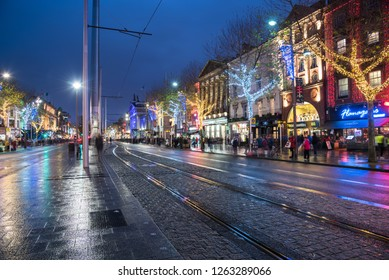 "Dublin, Ireland - December 8, 2018: O'Connell Street Decorated for Christmas and Crowed with Shoppers and Tourists alike. O'Connell Street is he home of the ""Spire"", the world's tallest sculpture."
