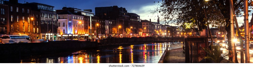 Dublin, Ireland. Embankment of Liffey River in Dublin, Ireland. Night view with buildings and city lights at the background
