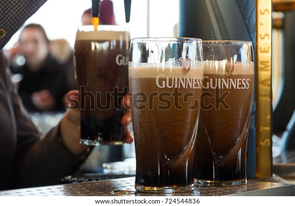 DUBLIN, IRELAND - FEB 15, 2014: Pints of beer are served at The Guinness Brewery on Feb 15, 2014. The brewery where 2.5 million pints of stout are brewed daily was founded by Arthur Guinness in 1759.