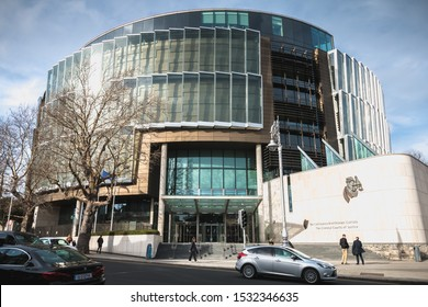 Dublin, Ireland - February 13, 2019: person walking in front of The Criminal Courts of Justice in the city center on a winter day