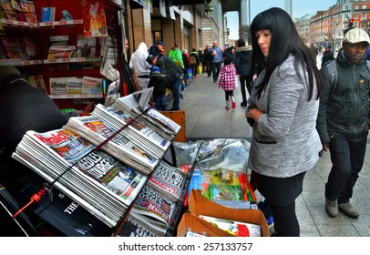 DUBLIN, IRELAND - FEBRUARY 19: A woman reads newspaper headlines at a newsstand along O'Connell Street on February 19, 2015 in Dublin, Ireland.