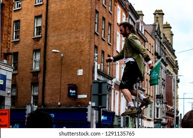 Dublin Ireland - February 20th 2018: A street performer is on a unicycle doing a performance on Grafton Street. Street performers in Ireland are common.