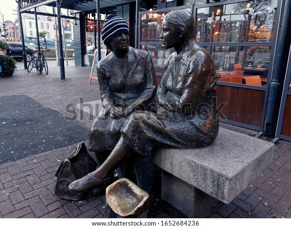 "DUBLIN, IRELAND - FEBRUARY 21, 2020: The statue of two women sitting on the bench, with somebody's hat put on. The ""Meeting place"" statue by Jakki McKenna, called by locals ""the hags with the bags""."