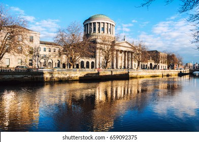 Dublin, Ireland. Four courts building in Dublin, Ireland with reflection in river Liffey during the sunny evening. cloudy blue sky