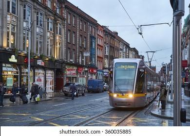 DUBLIN, IRELAND - JANUARY 05: The Luas, Dublin's tram system train, crossing pedestrian area in rainy day. January 05, 2016 in Dublin