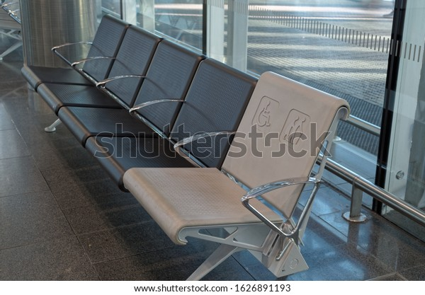 DUBLIN, IRELAND - JANUARY 15, 2020: Row of empty seats in airport hall with a seat allocated for people with disabilities. Close up view from above.