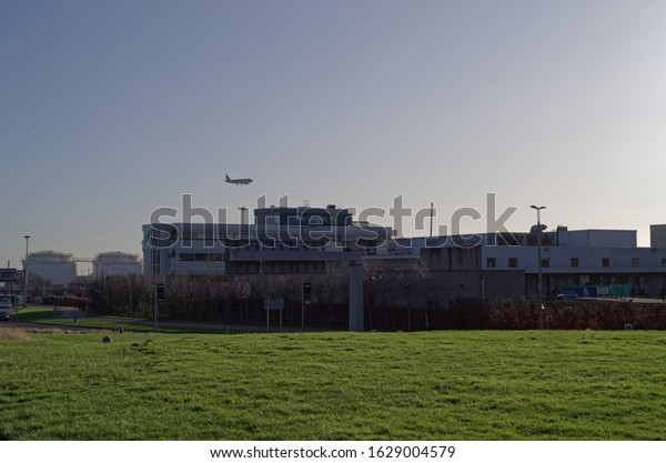 DUBLIN, IRELAND - JANUARY 15, 2020: A view of the Aer Lingus building, with landing Aer Lingus plane above. Dublin airport. Green grass field in the foreground.