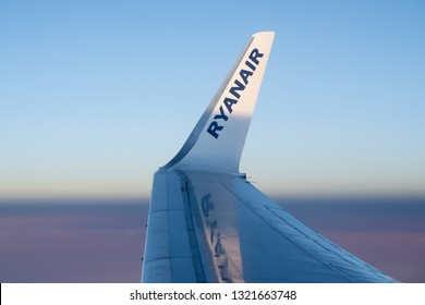 Dublin, Ireland - January 16 2016: RyanAir logo on wingtip of plane flying above the clouds seen from place window