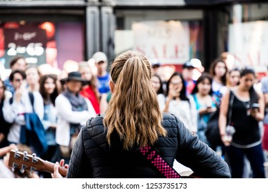 Dublin, Ireland - July 4, 2018: A street performer sings in front of an audience
