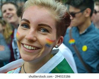 DUBLIN, IRELAND - JUNE 27: A pretty female participant with rainbows painted on her cheeks during the Dublin Pride Parade on June 27, 2015 in Dublin, Ireland.