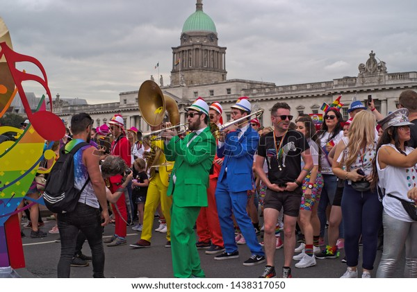 DUBLIN, IRELAND - JUNE 29, 2019: Musicians in colorful uniforms play for people in Dublin Pride Parade.