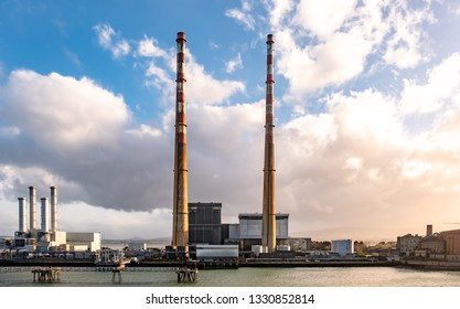 DUBLIN / IRELAND - MARCH 03 2019: Poolbeg power station in the harbour producing during sunset.