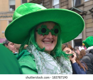 DUBLIN, IRELAND - MARCH 17: An unidentified smiling female spectator wearing a huge green hat and dyed green hair attends the annual St. Patrick's Day Parade on March 17, 2014 in Dublin, Ireland.
