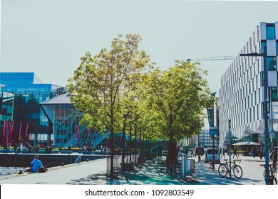 DUBLIN, IRELAND - May 16th, 2018: detail of Grand Canal Square with trees, bikes and pedestrian on the affluent side of Dublin Docklands