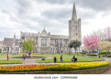 DUBLIN, IRELAND - MAY 5, 2016: People enjoying the park in front of the St Patrick's Cathedral. It is the largest church in Ireland and every November it hosts the Ireland's Remembrance Day ceremonies