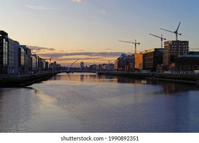 DUBLIN, IRELAND - Oct 27, 2019: Sunset over River Liffey in Dublin, Ireland with the Samuel Beckett Bridge in the frame