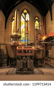 DUBLIN, IRELAND. OCTOBER 03, 2018. Pot Still equipment at the altar of an St James Church, with stained glass in the background, at Pearse Lyons Distillery.