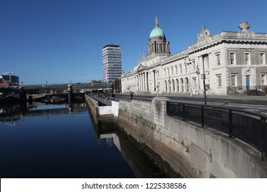 Dublin, Ireland - October 18, 2018: Looking west over Liffey River showing dome and facade of old Custom House and new IFSC, International Finance Service Center, building. Street and cloudscape.