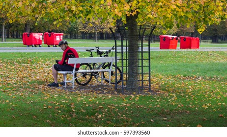 "DUBLIN, IRELAND - OCTOBER 2016 -  A unidentified man taking a brake on a bench besides his bike at through ""Phoenix Park"" on October 2016 in Dublin."