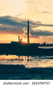 Dublin / Ireland - October 2019 : One the most recognisable Dublin landmark - Poolbeg Pigeon House Power Station chimney reflects in the water during a spectacular sunset time.