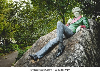 Dublin, Ireland - September, 21 2018: Wonderful statue of famous writer Oscar Wilde on huge boulder near alley in Trinity Park