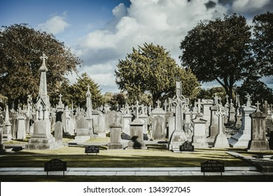 Dublin, Ireland - September, 23 2018: Row of weathered gravestones against blue sky on sunny day on Glasnevin Cemetery