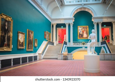 Dublin, Ireland - September, 24 2018: Various classic artworks hanging on walls of spacious showroom with beautiful statue in National Gallery