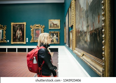 Dublin, Ireland - September, 24 2018: Side view of young female with backpack looking at beautiful artwork in spacious showroom of National Gallery