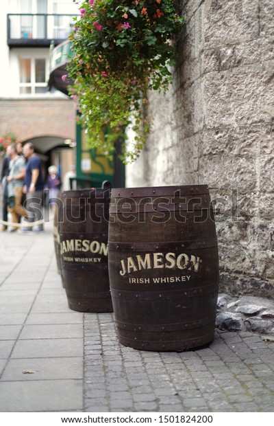 DUBLIN, IRELAND - SEPTEMBER 4, 2019: A side view of Jameson Irish Whiskey barrels staying next to stone wall. Blur background.