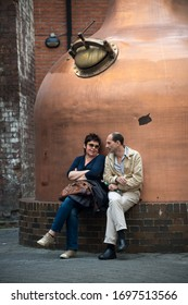 DUBLIN, IRELAND-SEPTEMBER 13, 2014: Tourists resting after a hectic sightseeing schedule at the Old Jameson Distillery, Dublin, in front of whisky stills.