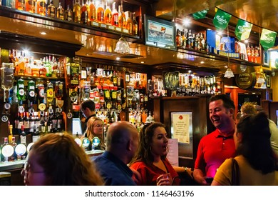 DUBLIN - JULY 14, 2018: Interior of pub, for drinking and socializing, focal point of community Dublin, Ireland. Pub business, now about 53,500 pubs in the UK, has been declining every y
