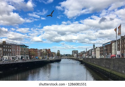 DUBLIN, LEINSTER, IRELAND - MAY 13, 2018: Liffey river and Millenium Bridge from Grattan Bridge in downtown Temple Bar area. This cheerful point is central to tourists visiting Ireland's capital city.