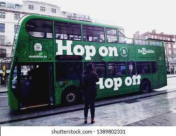 Dublin/Ireland - January 3,2019 : A local woman stading at the bus stop with DoDublin green Hop-on Hop-off bus in center of Dublin City