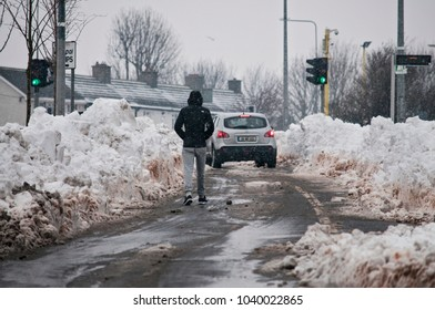 DUBLIN.IRELAND - March 03 , 2018: Ð¡ity roads in snowdrifts as a result of a snow storm in Ireland. All sidewalks covered with snow and pedestrians walk along the roadway .