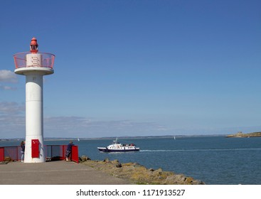 Dublin,Ireland,04/09/2018.People standing beside the lighthouse in Howth, Dublin,Ireland, watching a Dublin Bay Cruise ship entering Howth Harbour.