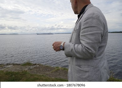 Dubna / Russia - August 24, 2020: Heavy-set man in a wrinkled mini houndstooth linen jacket looking out to a ship moored off the coast