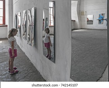 DUBNO, UKRAINE - JULY 30, 2017: The unidentified girl looking at her image in the distorted mirror in the hall of mirrors at the 30th of July, 2017 in Dubno, Ukraine