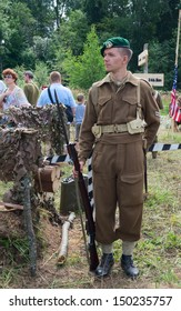 DUBOSEKOVO, RUSSIA - JULY 13: a military history club member in British WWII commando uniform guards the camp during Field of Battle military history festival on July 13, 2013 in Dubosekovo, Russia