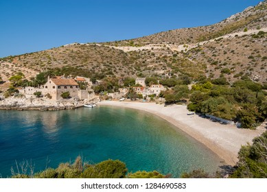 Dubovica beach in the Adriatic Sea on the island of Hvar. The pebble beach is sheltered in an emerald green lagoon set against a small cluster of historic stone houses nestled among rolling hills.