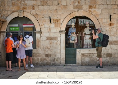 DUBROVNIK, CROATA-July 1, 2029: Tourists loitering in Old Town Dubrovnik, some using ATM, a girl snapping on her phone and avideographer documenting the surroundings