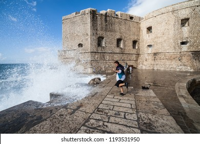 Dubrovnik, Croatia - 26 September, 2010: Medieval walls of Dubrovnik city, Old Town fortification, surprised tourist woman by splashing wave on pier by the Adriatic Sea, UNESCO World Heritage Site