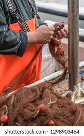 Dubrovnik, Croatia - April 2018 : Fisherman disentangling fish caught in the net